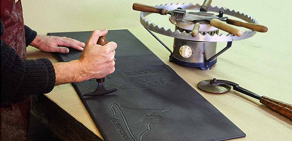 Master Binder Keith Felton uses hand-tools to decorate the leather covers of ANTARCTICA. A collection of these tools are kept warm on the heater called a Finishing Stove