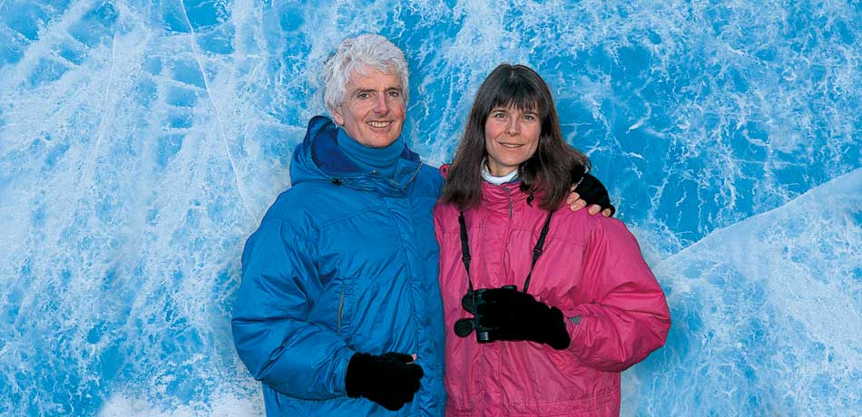 Portrait of Pat and Rosemarie Keough in winter clothing in front of a wall of solid blue ice marbled with white fissures
